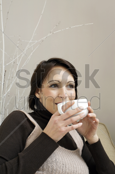 woman sitting on the couch holding a cup of coffee stock photo