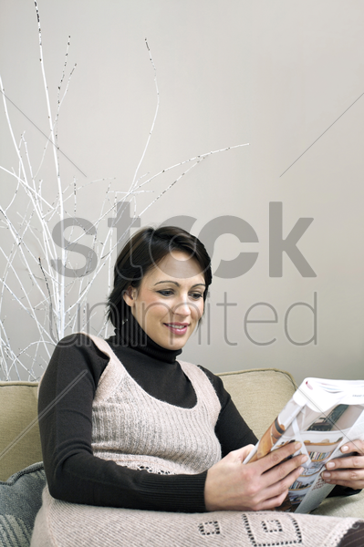 woman sitting on the couch reading magazine stock photo