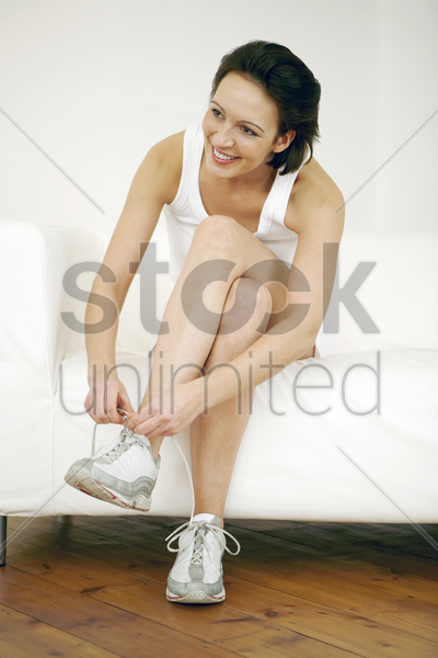 woman sitting on the couch tying her shoelace stock photo