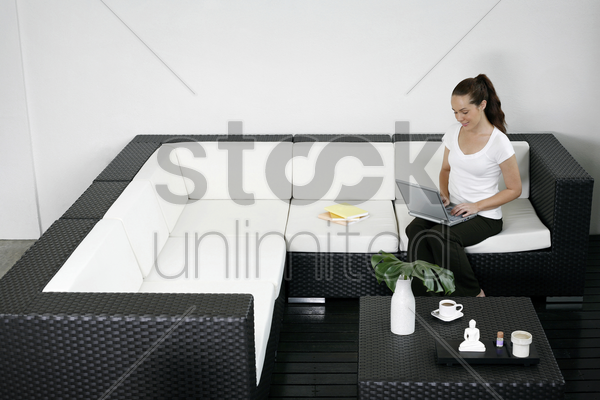 woman sitting on the couch using laptop stock photo