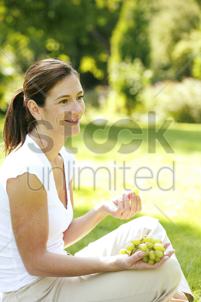woman sitting on the field eating green grapes stock photo