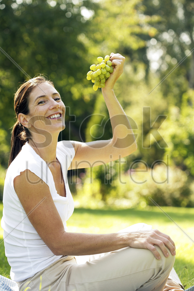 woman sitting on the field holding green grapes stock photo