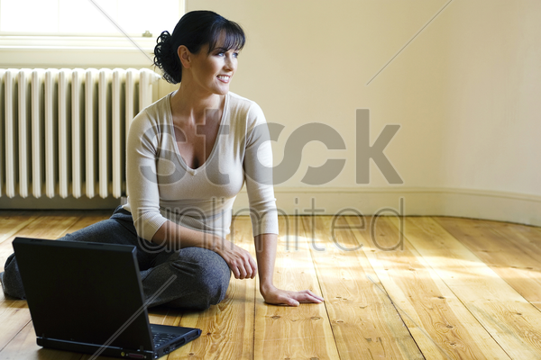 woman sitting on the floor with laptop in front of her stock photo