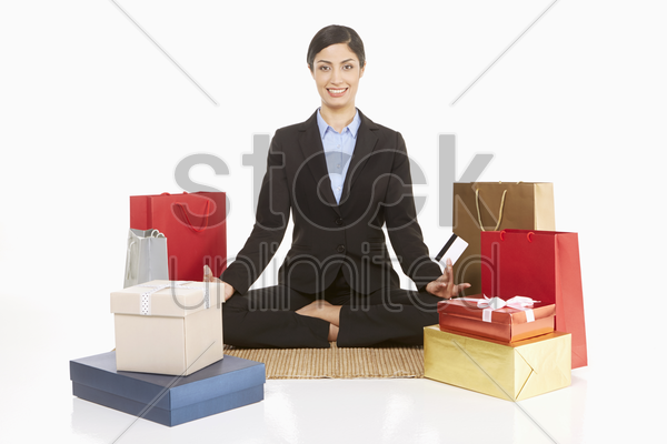 woman sitting on the floor with shopping items, holding credit card stock photo