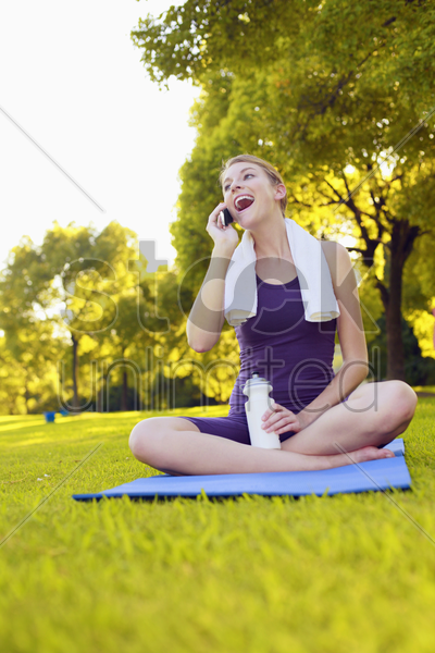 woman sitting on yoga mat and talking on the phone stock photo