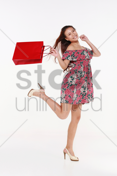 woman skipping happily after shopping stock photo