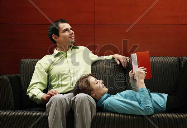 woman sleeping on her boyfriend's lap reading stock photo