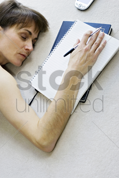 woman sleeping on the floor while doing work stock photo