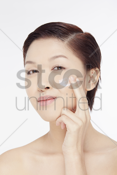 woman smearing lotion on her face stock photo