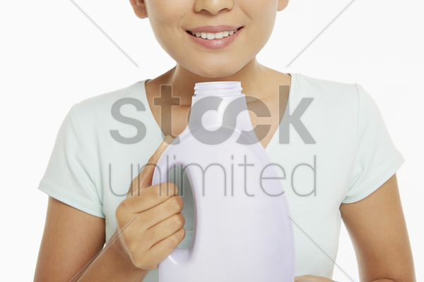 woman smelling a bottle of detergent stock photo
