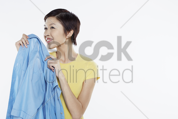 woman smelling a clean blouse stock photo