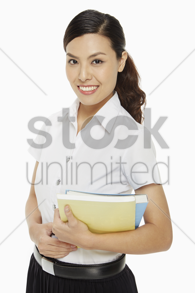 woman smiling and carrying books stock photo