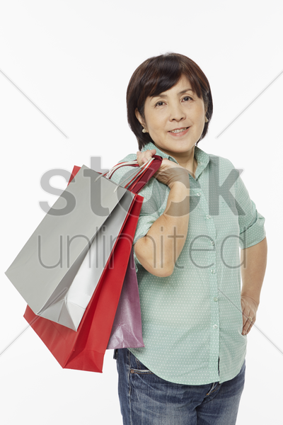 woman smiling and carrying shopping bags stock photo