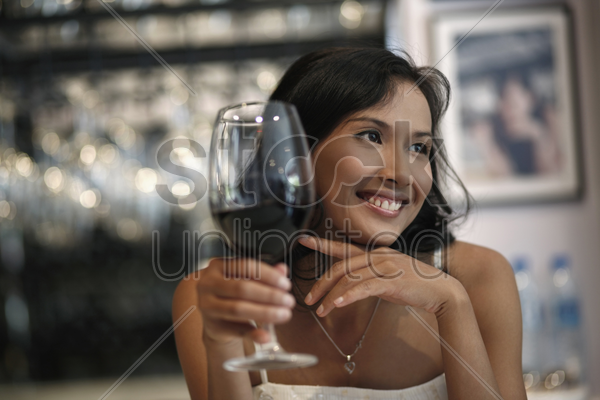 woman smiling and holding a glass of red wine stock photo