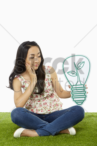woman smiling and holding up a cardboard light bulb stock photo