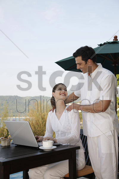 woman smiling and looking at man while using laptop stock photo