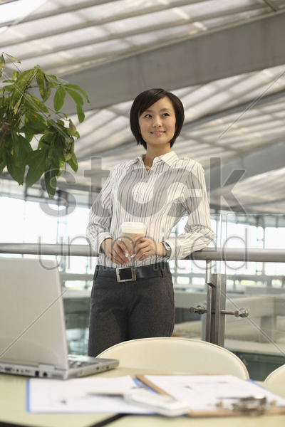 woman smiling and looking away while holding a cup of coffee stock photo