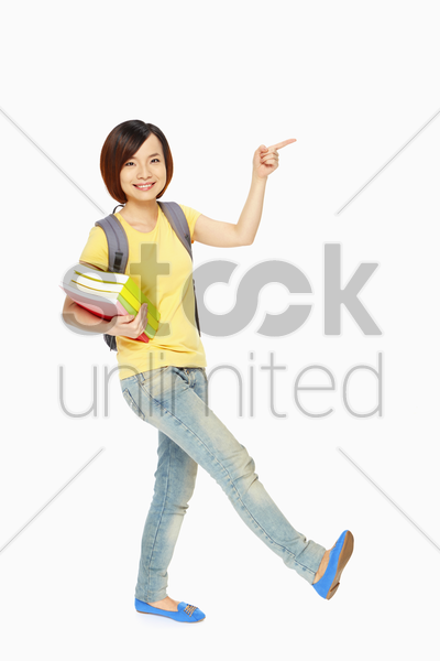 woman smiling and pointing to the left stock photo