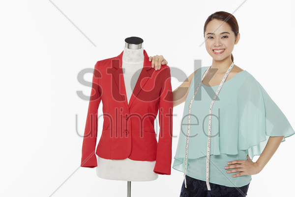woman smiling and standing beside a mannequin stock photo