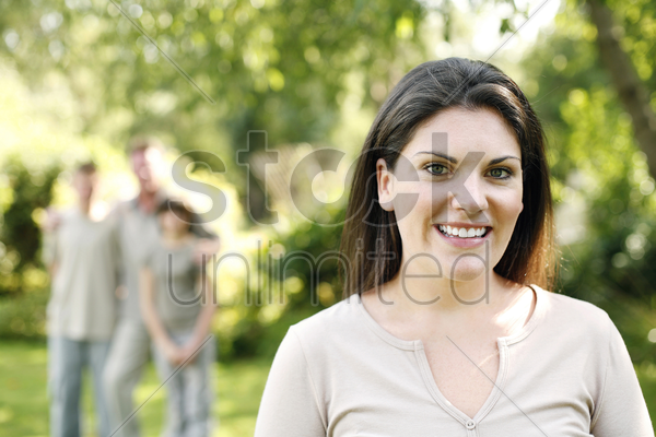 woman smiling at the camera with her family standing in the background stock photo