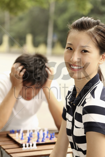 woman smiling, man with hands on head in the background stock photo