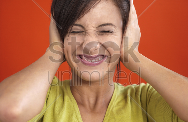 woman smiling while closing her ears stock photo