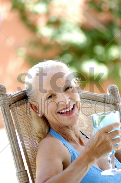 woman smiling while holding a glass of drink stock photo