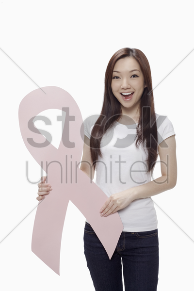 woman smiling while holding a pink breast cancer ribbon stock photo