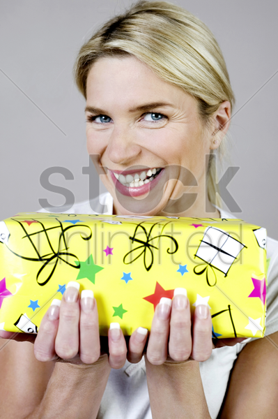 woman smiling while holding a present stock photo