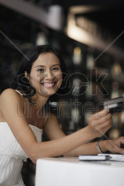 woman smiling while holding credit card stock photo