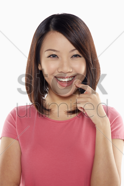 woman smiling while holding up index finger stock photo