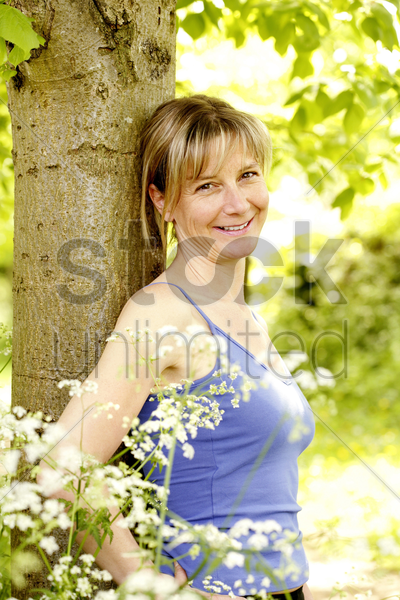 woman smiling while leaning against a tree stock photo