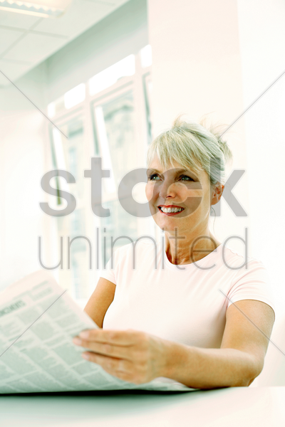 woman smiling while reading newspaper stock photo