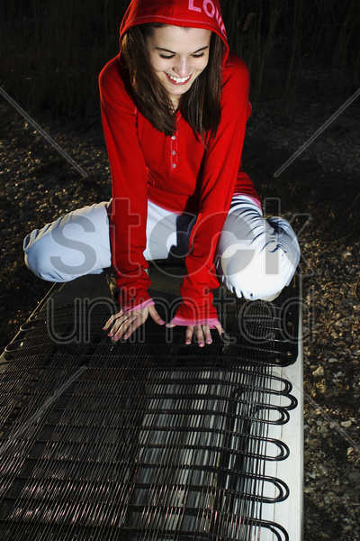 woman smiling while sitting on the back of a fridge stock photo
