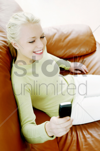 woman smiling while text messaging on the mobile phone stock photo