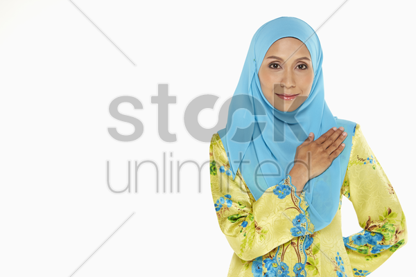 woman smiling with palm placed on chest stock photo
