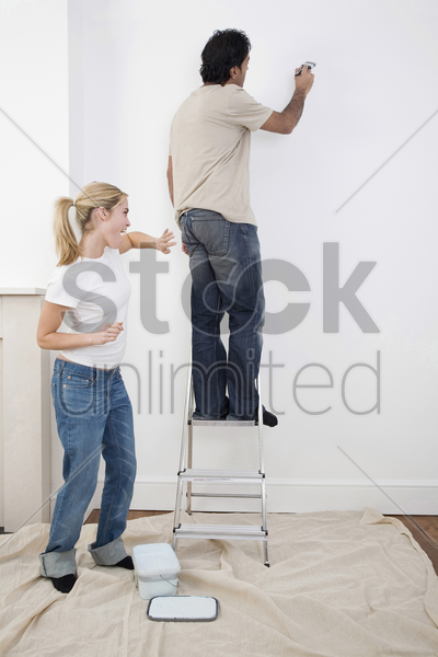 woman spanking boyfriend's back side with her paint covered hand stock photo