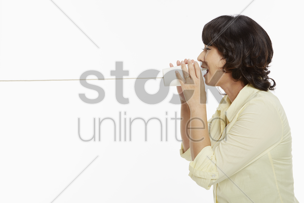 woman speaking into a cup phone stock photo