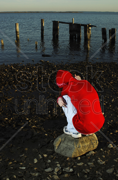 woman squatting on a rock stock photo
