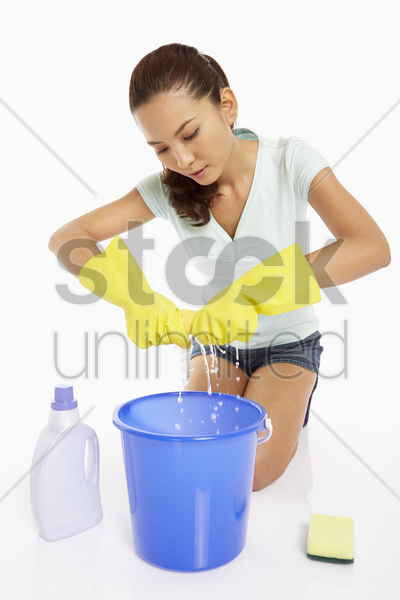 woman squeezing water out from the cloth stock photo