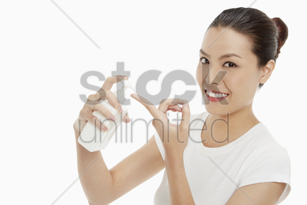 woman squirting lotion onto her finger stock photo