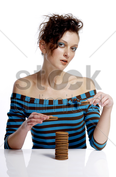 woman stacking up biscuits stock photo