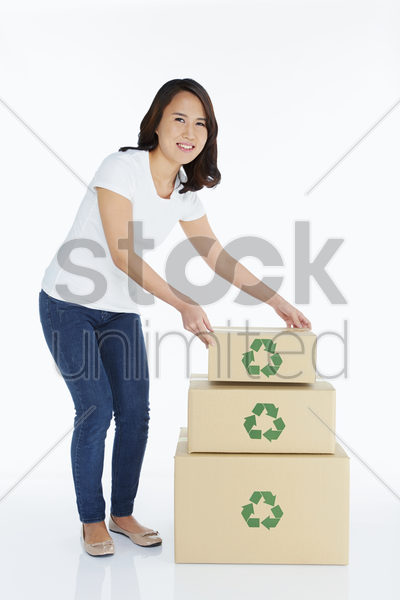 woman stacking up cardboard boxes stock photo