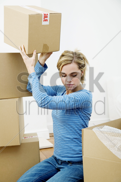 woman stacking up sealed boxes stock photo
