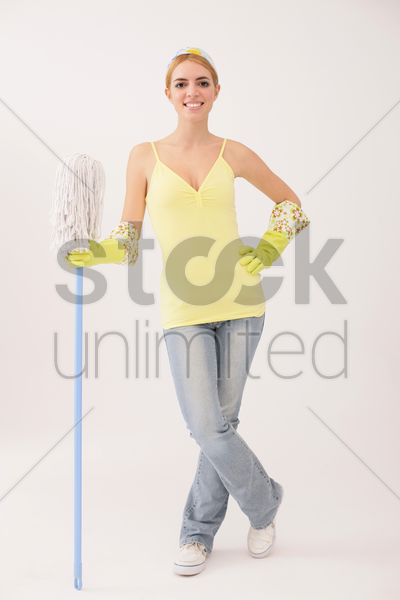 woman standing and holding mop stock photo
