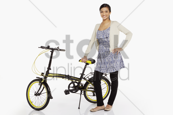woman standing beside a bicycle stock photo