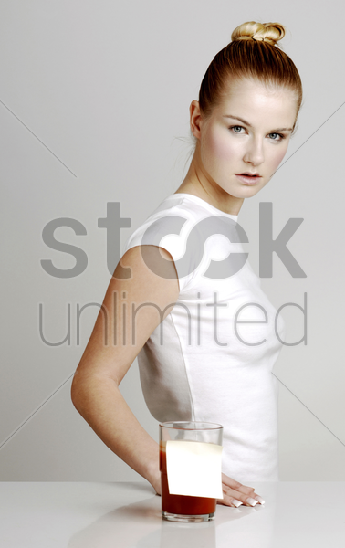 woman standing beside a glass of drink with reminder note stock photo
