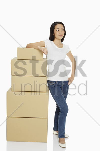 woman standing beside a stack cardboard boxes stock photo