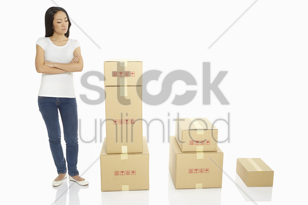 woman standing beside a stack of cardboard boxes, contemplating stock photo
