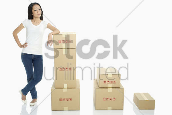 woman standing beside a stack of cardboard boxes stock photo